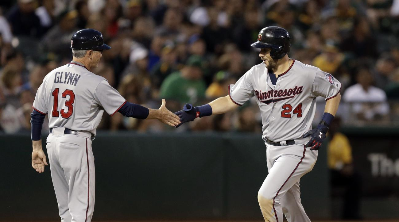 Minnesota Twins' Trevor Plouffe, right, celebrates with third base coach Gene Glynn (13) after Plouffe hit a grand slam off Oakland Athletics' Sonny Gray during the sixth inning of a baseball game Friday, July 17, 2015, in Oakland, Calif. (AP Photo/Ben Ma