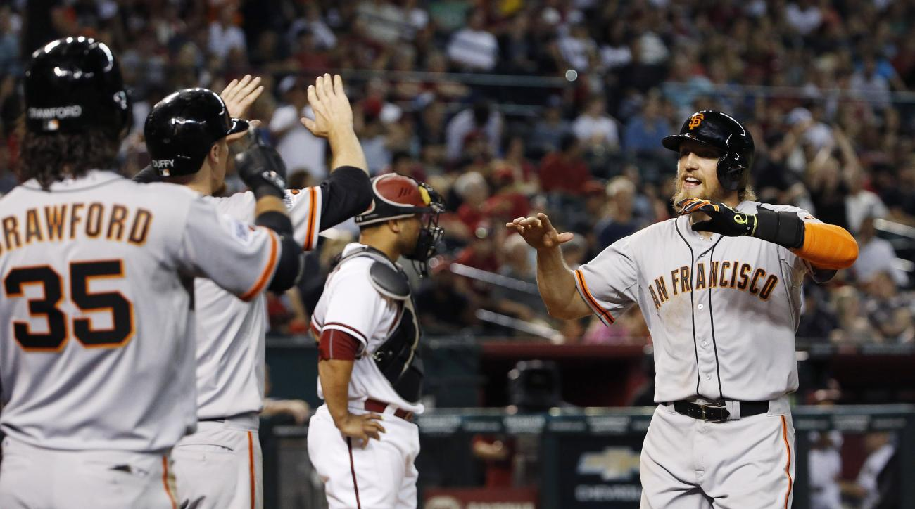 San Francisco Giants' Hunter Pence, right, celebrates his two-run home run with teammates Brandon Crawford (35) and Matt Duffy, second from left, as Arizona Diamondbacks' Welington Castillo stands at home plate during the seventh inning of a baseball game