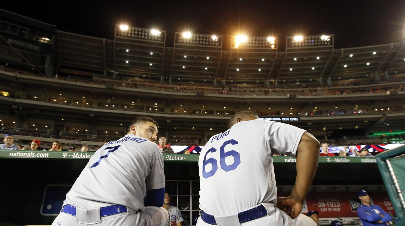 Los Angeles Dodgers' Alex Guerrero (7) and right fielder Yasiel Puig (66) sit on the edge of the dugout under the lights that are out, as play was halted for the second time, during the fifth inning of a baseball game against the Washington Nationals at N