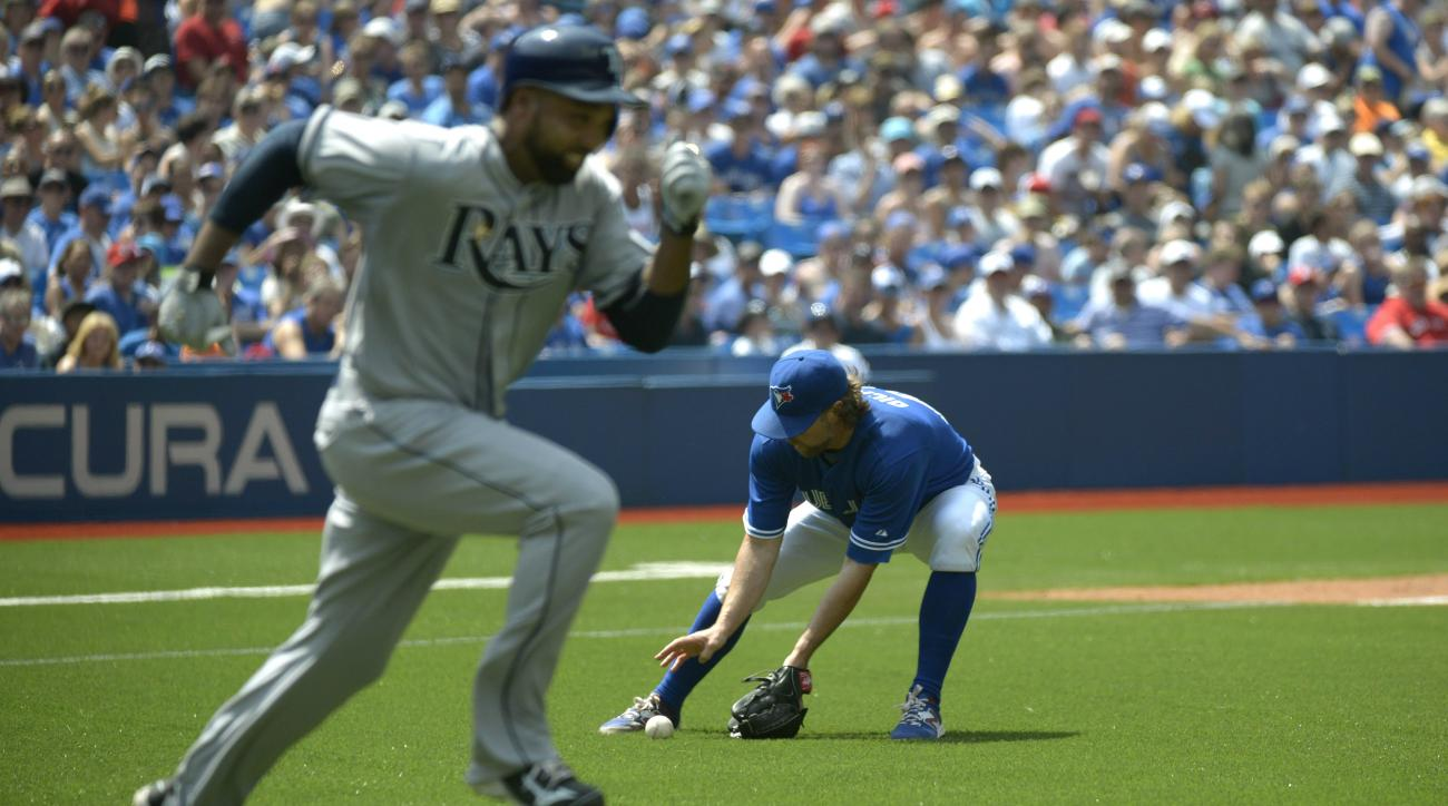 Toronto Blue Jays' pitcher R.A. Dickey, right, fields a ground ball off the bat of Tampa Bay Rays' Joey Butler and makes the out at first during the sixth inning of a baseball game Saturday, July 18, 2015, in Toronto. (Jon Blacker /The Canadian Press via