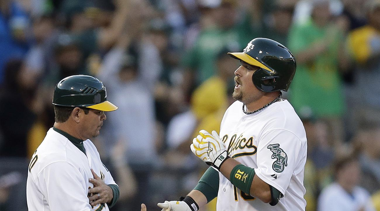 Oakland Athletics' Billy Butler, right, is congratulated by third base coach Mike Gallego after hitting a home run off Minnesota Twins' Phil Hughes in the seventh inning of a baseball game Saturday, July 18, 2015, in Oakland, Calif. (AP Photo/Ben Margot)