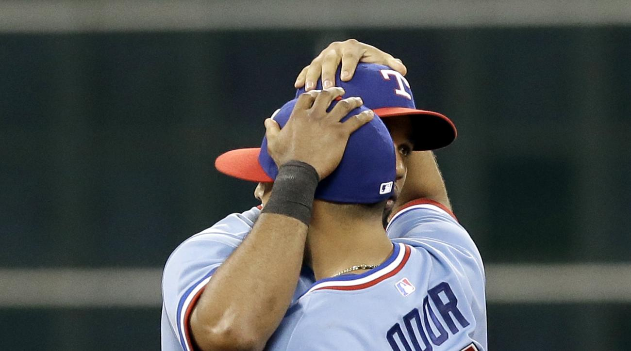 Texas Rangers' Rougned Odor (12) and Elvis Andrus hug after they defeated the Houston Astros 7-6 in a baseball game Saturday, July 18, 2015, in Houston. (AP Photo/Pat Sullivan)