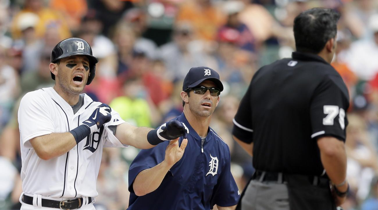 Detroit Tigers manager Brad Ausmus, center, holds back Tigers' Ian Kinsler as they argue a call with home plate umpire Manny Gonzalez during the third inning of a baseball game against the Baltimore Orioles, Sunday, July 19, 2015, in Detroit. (AP Photo/Ca