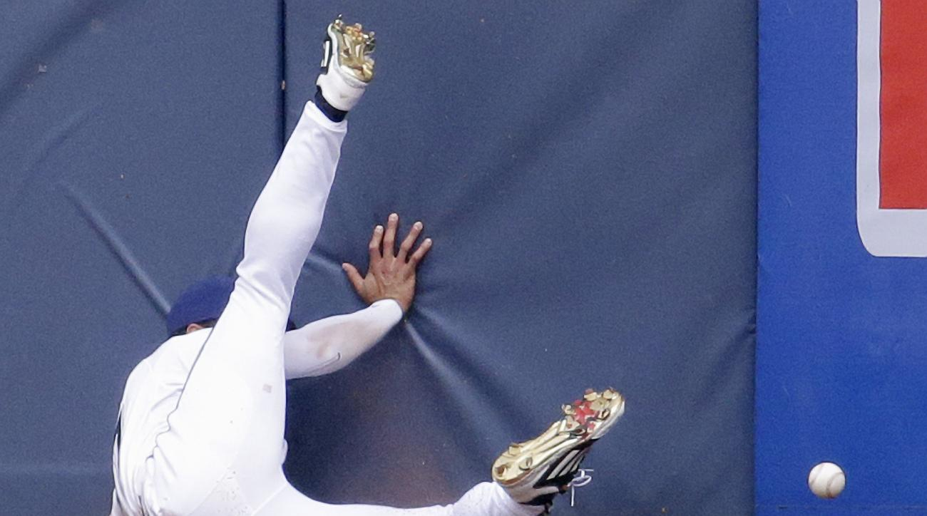 Milwaukee Brewers center fielder Carlos Gomez can't catch a ball hit by Pittsburgh Pirates' Jaff Decker during the fifth inning of a baseball game Sunday, July 19, 2015, in Milwaukee. (AP Photo/Morry Gash)