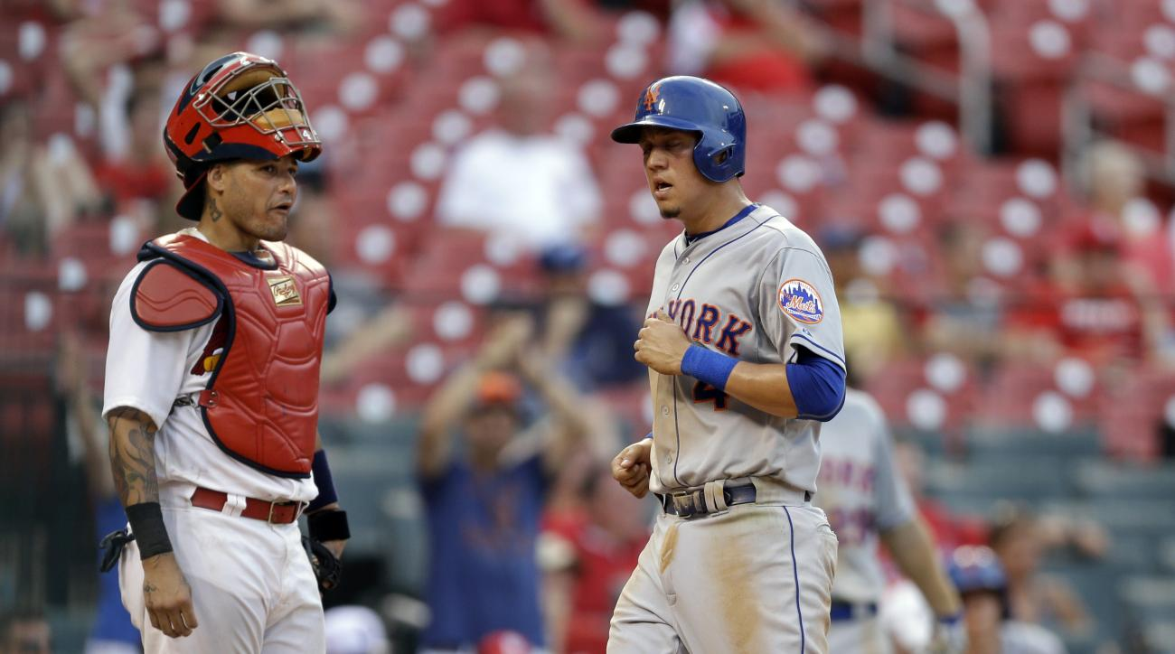 New York Mets' Wilmer Flores, right, scores past St. Louis Cardinals catcher Yadier Molina on a sacrifice fly by Ruben Tejada during the 18th inning of a baseball game Sunday, July 19, 2015, in St. Louis. (AP Photo/Jeff Roberson)