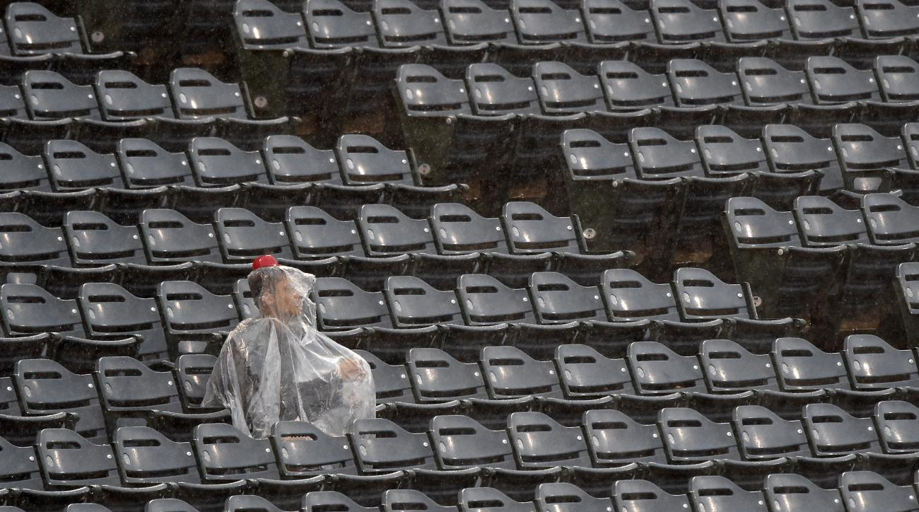 A lone fan sits in the rain during a rain delay prior to a baseball game between the Los Angeles Angels and the Boston Red Sox, Sunday, July 19, 2015, in Anaheim, Calif. (AP Photo/Mark J. Terrill)