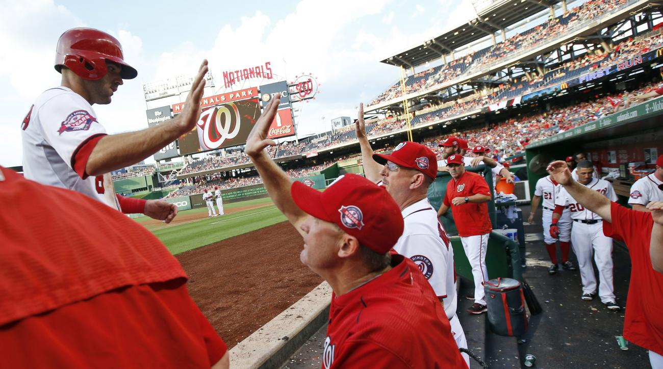 Washington Nationals' Danny Espinosa, left, celebrates scoring with bench coach Randy Knorr, second from left, and others, during the first inning of a baseball game against the New York Mets at Nationals Park, Monday, July 20, 2015, in Washington. (AP Ph