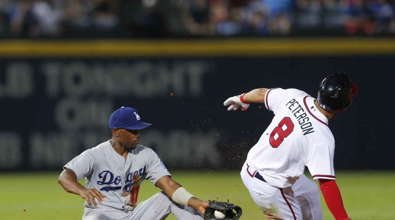 Atlanta Braves' Jace Peterson (8) is tagged out by Los Angeles Dodgers shortstop Jimmy Rollins as he tries to stretch a single in the sixth inning of a baseball game Monday, July 20, 2015, in Atlanta. (AP Photo/John Bazemore)