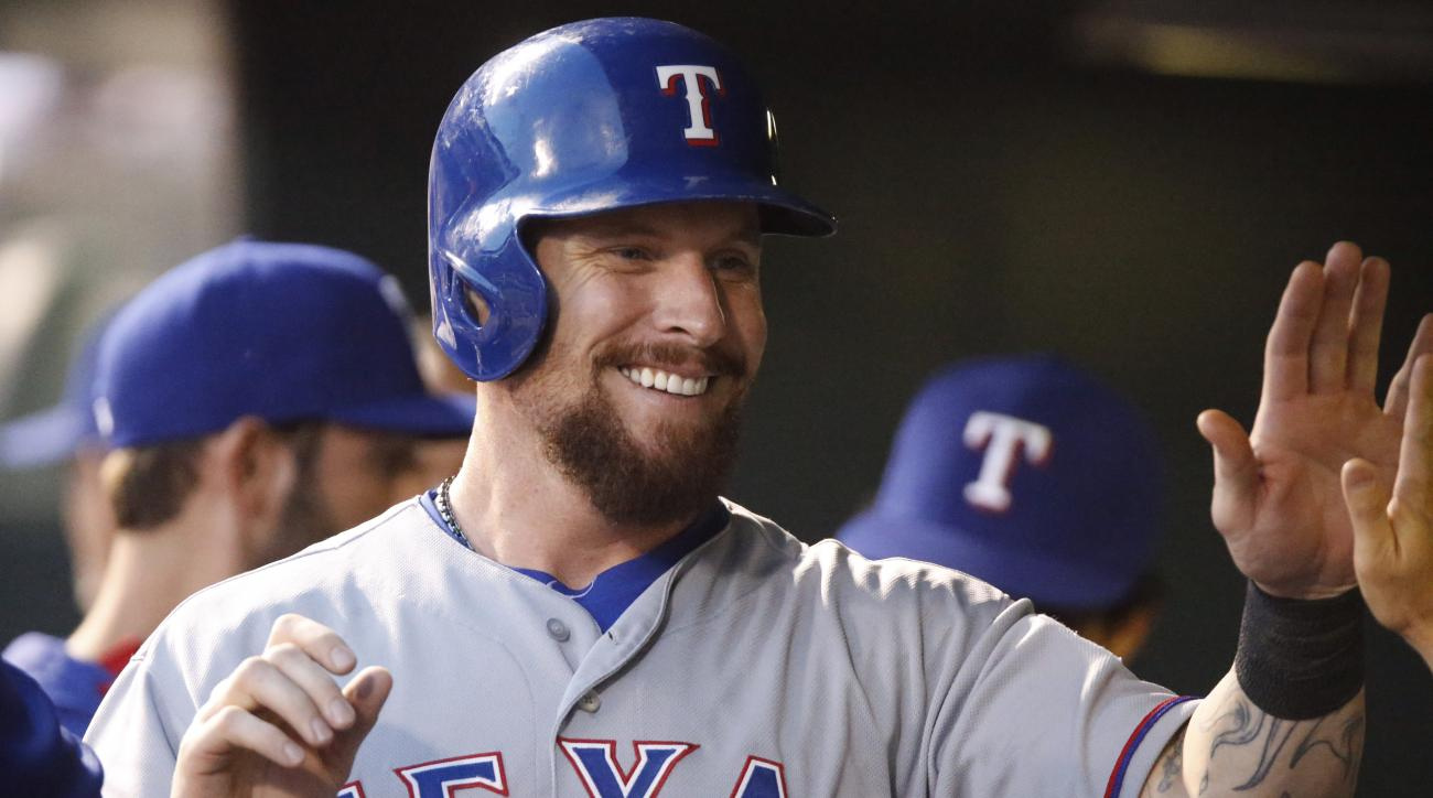 Texas Rangers' Josh Hamilton is congratulated by teammates after scoring on single hit by Shin-Soo Choo off Colorado Rockies relief pitcher Yohan Flande in the fifth inning of an inter league baseball game Tuesday, July 21, 2015, in Denver. (AP Photo/Davi