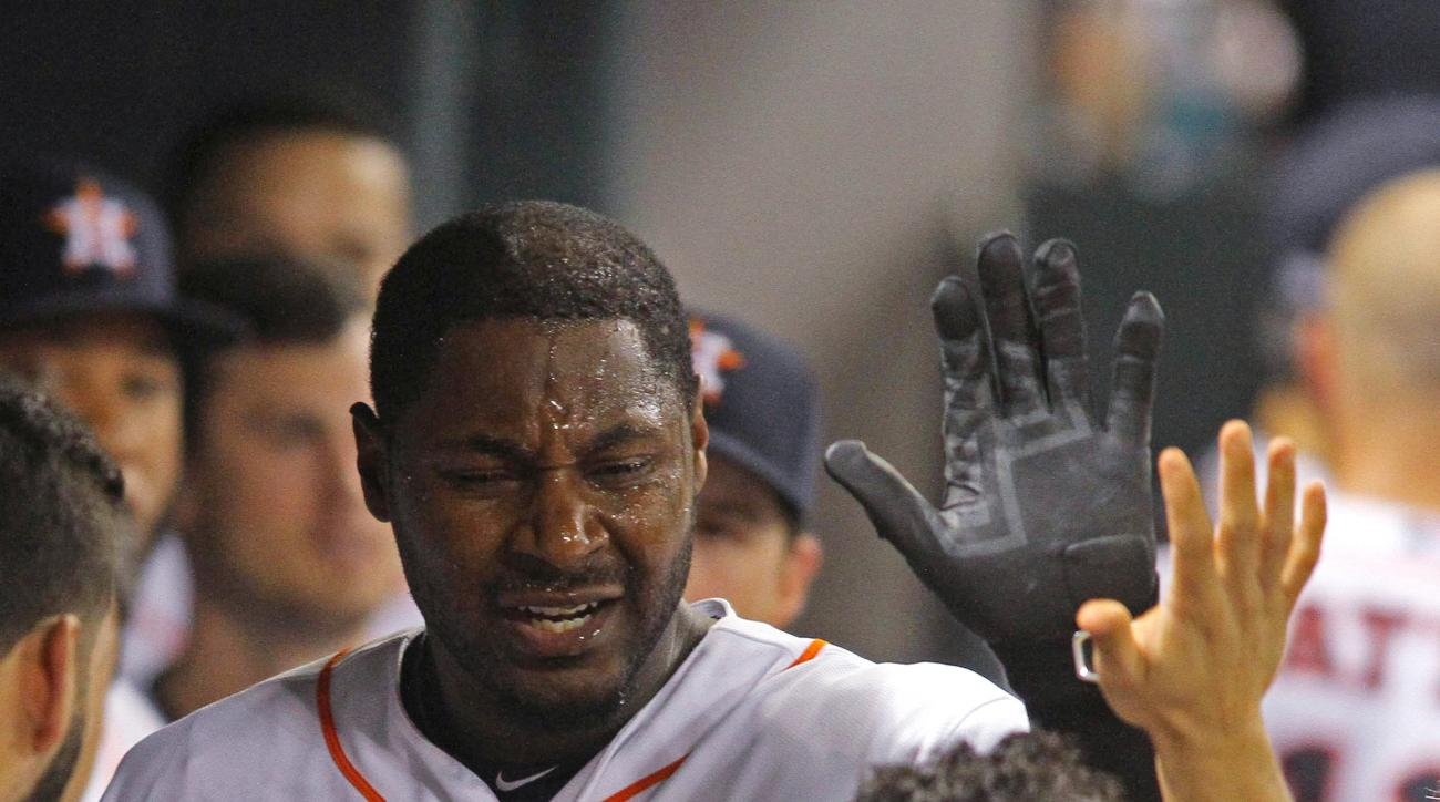 Houston Astros' Chris Carter greets teammate Jose Altuve in the dugout after Carter's home run against the Boston Red Sox during the sixth inning of a baseball game Tuesday, July 21, 2015, in Houston.  (AP Photo/Richard Carson)