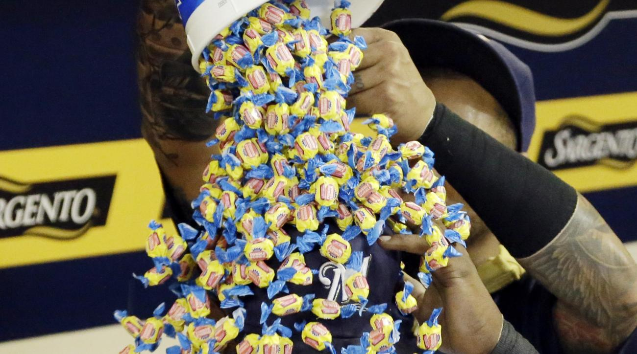 Milwaukee Brewers' Martin Maldonado pours  bubble gum on teammate Jean Segura (9) during a TV interview after a baseball game against the Cleveland Indians Tuesday, July 21, 2015, in Milwaukee. The Brewers won 8-1. (AP Photo/Morry Gash)