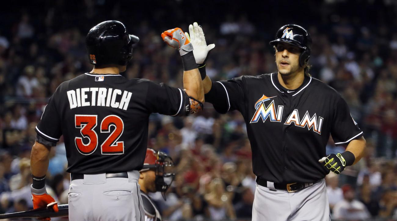 Miami Marlins' Michael Morse is greeted by teammate Derek Dietrich (32) after hitting a solo home run against the Arizona Diamondbacks during the seventh inning of a baseball game, Tuesday, July 21, 2015, in Phoenix. (AP Photo/Matt York)