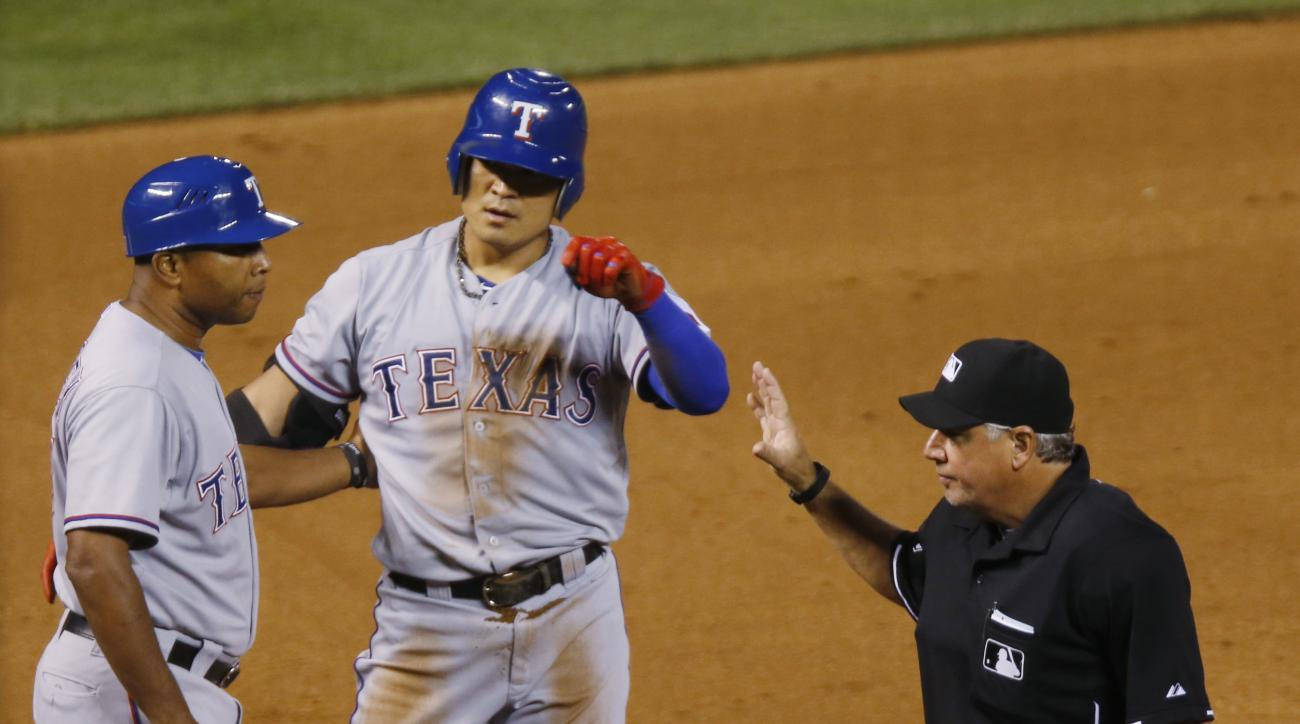 Texas Rangers third base coach Tony Beasley, left, congratulates Shin-Soo Choo after he hit a triple to complete the cycle, during the ninth inning of a baseball game against the Colorado Rockies on Tuesday, July 21, 2015, in Denver. (AP Photo/David Zalub