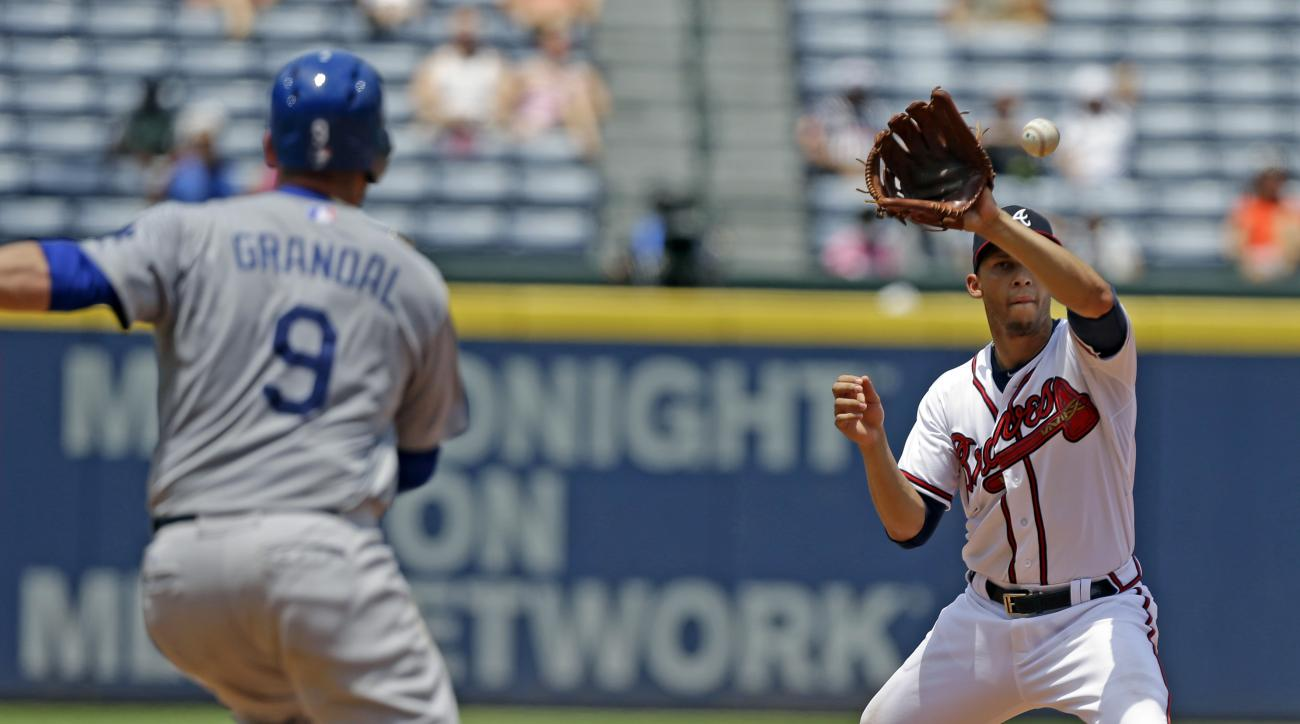 Atlanta Braves shortstop Andrelton Simmons (19) gets the force out on a double play as Los Angeles Dodgers' Yasmani Grandal (9) runs to second during the sixth inning of a baseball game, Wednesday, July 22, 2015, in Atlanta. (AP Photo/Butch Dill)