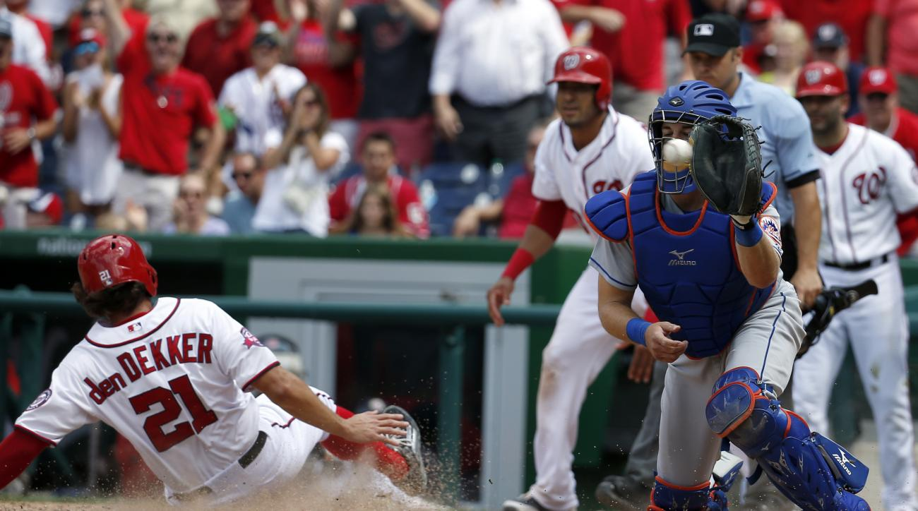 CORRECTS SCORE TO 4-3 - Washington Nationals' Matt den Dekker (21) slides safely home on a Michael Taylor single, as New York Mets catcher Kevin Plawecki (22) waits for the throw during the eighth inning of a baseball game at Nationals Park, Wednesday, Ju