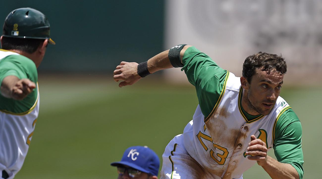 FILE - In this June 27, 2015, file photo, Oakland Athletics' Sam Fuld, right, runs to score past Kansas City Royals third baseman Mike Moustakas, center, in the first inning of a baseball game in Oakland, Calif. After nearly eight years in the majors, Ful