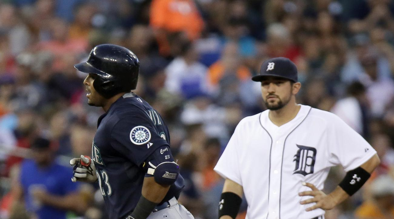 Seattle Mariners' Nelson Cruz, left, rounds the bases past Detroit Tigers third baseman Nick Castellanos after hitting a solo home run during the sixth inning of a baseball game Wednesday, July 22, 2015, in Detroit. (AP Photo/Duane Burleson)