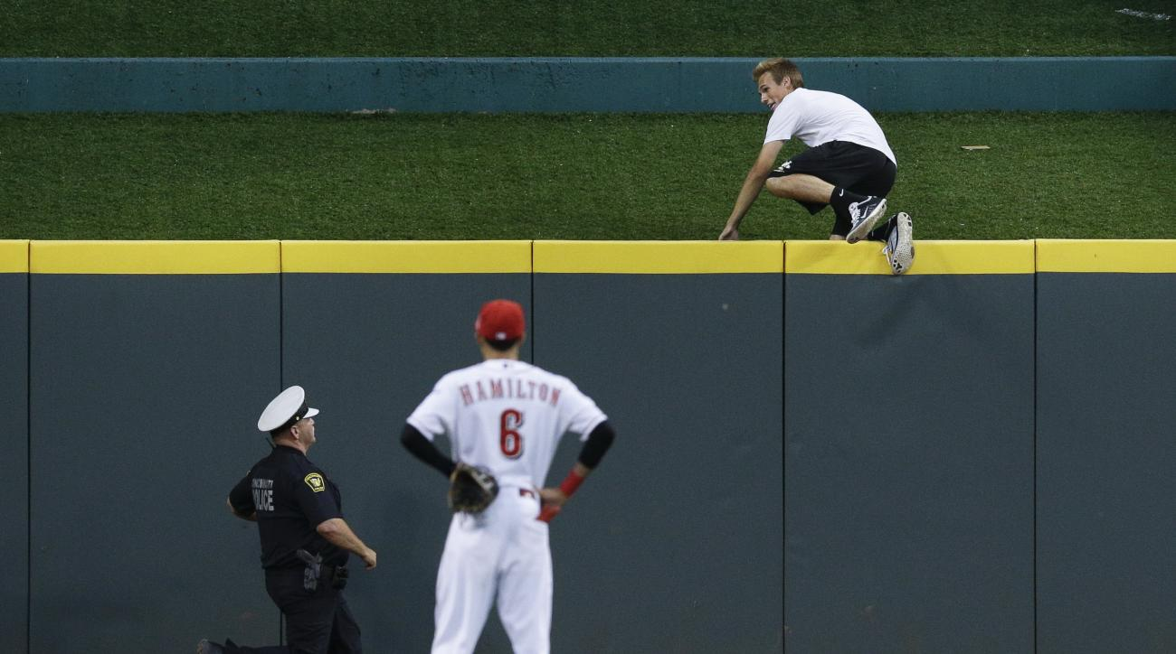 A fan jumps over the center field wall as he evades police while Cincinnati Reds center fielder Billy Hamilton (6) looks on in the eighth inning in the second game of a baseball doubleheader against the Chicago Cubsin Cincinnati, Wednesday, July 22, 2015.