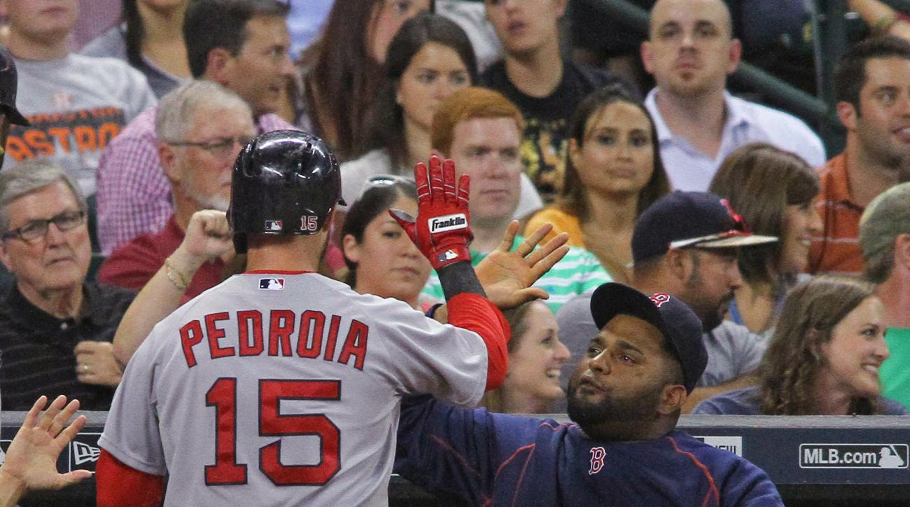 Boston Red Sox's Dustin Pedroia is greeted in the dugout by Pablo Sandoval after scoring against the Houston Astros during the sixth inning of a baseball game Wednesday, July 22, 2015, in Houston. (AP Photo/Richard Carson)