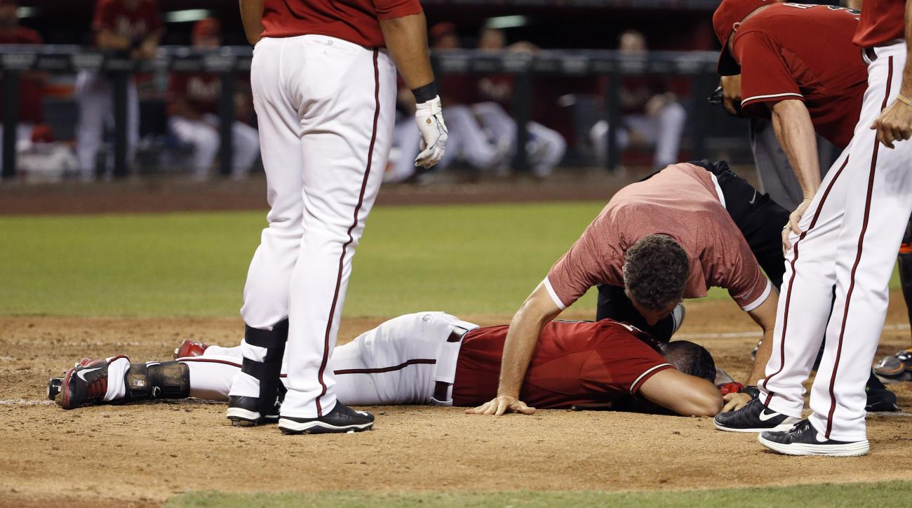 Arizona Diamondbacks' David Peralta is attended to by Diamondbacks training staff as he stays motionless on the ground after being hit in the head by a pitch during the sixth inning of a baseball game Wednesday, July 22, 2015, in Phoenix. Peralta got up u