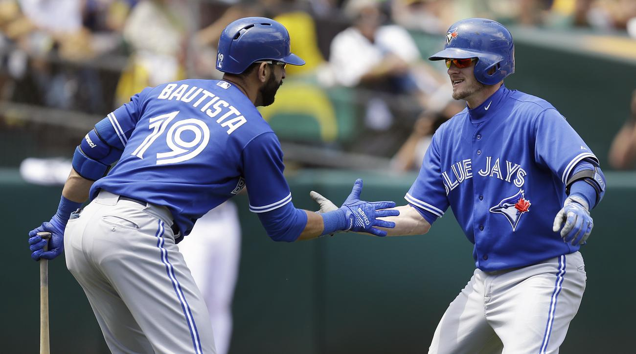 Toronto Blue Jays' Josh Donaldson, right, is congratulated by teammate Jose Bautista (19) after hitting a home run off Oakland Athletics' Dan Otero in the fifth inning of a baseball game Thursday, July 23, 2015, in Oakland, Calif. (AP Photo/Ben Margot)