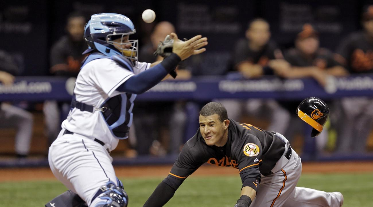 Baltimore Orioles' Manny Machado, right, slides home safely as the ball skips away from Tampa Bay Rays catcher Rene Rivera during the fourth inning of a baseball game Friday, July 24, 2015, in St. Petersburg, Fla. Machado scored on an RBI-double by Chris