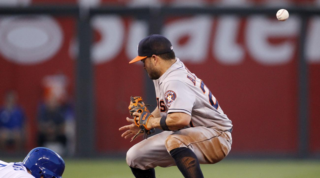 Houston Astros second baseman Jose Altuve, right, is unable to hold onto a throw from pitcher Scott Kazmir as Kansas City Royals' Mike Moustakas, left, dives back to second base on a pickoff attempt in the fourth inning of a baseball game in Kansas City,