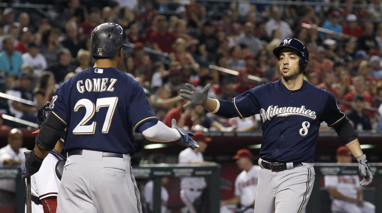 Milwaukee Brewers' Ryan Braun (8) reaches out to shake hands with Carlos Gomez (27) after Braun hit a home run against the Arizona Diamondbacks during the sixth inning of a baseball game Friday, July 24, 2015, in Phoenix. (AP Photo/Ross D. Franklin)