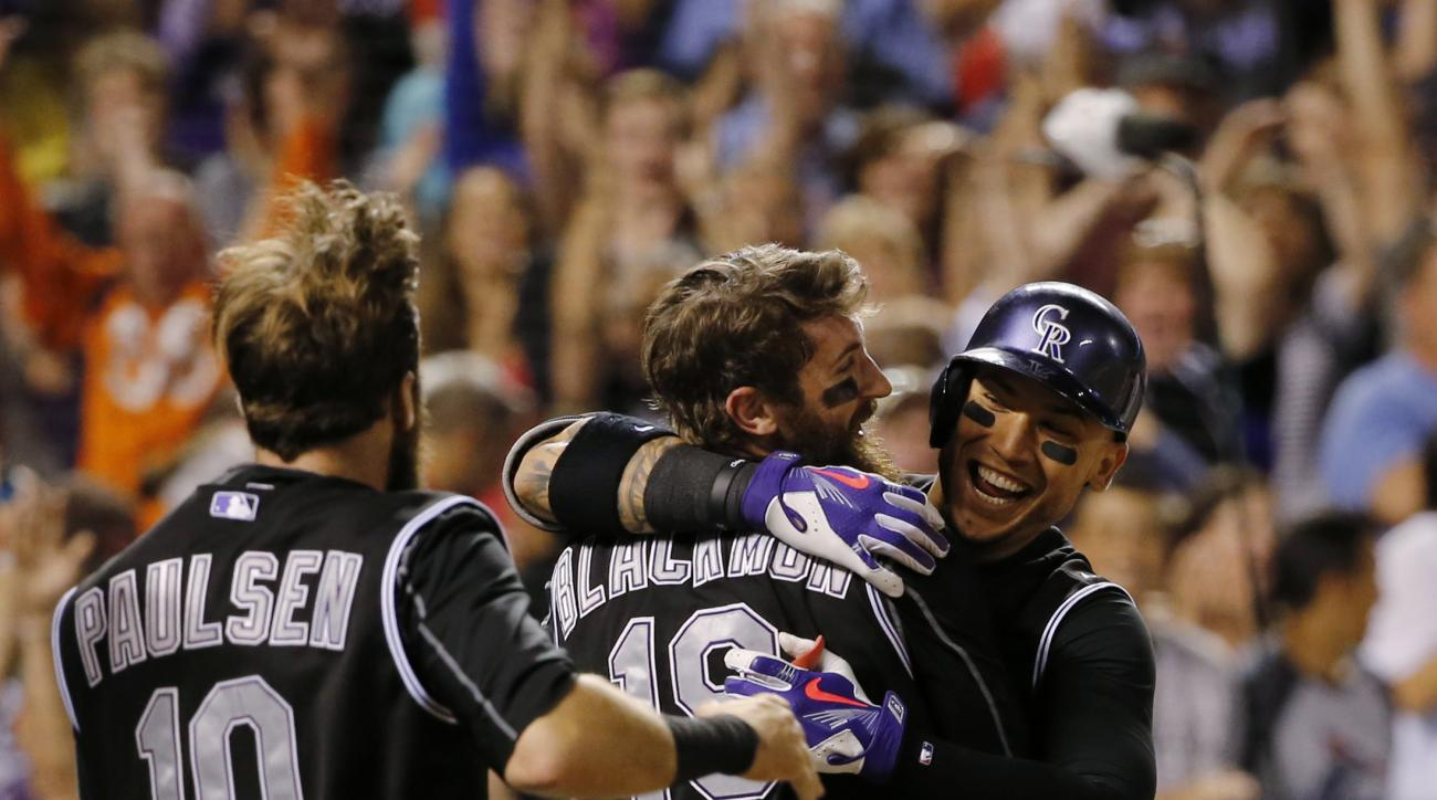 Colorado Rockies' Charlie Blackmon (19) is congratulated by teammates Carlos Gonzalez and Ben Paulsen (10) after scoring the game-winning run against the Cincinnati Reds during the ninth inning of a baseball game, Friday, July 24, 2015, in Denver. The Roc