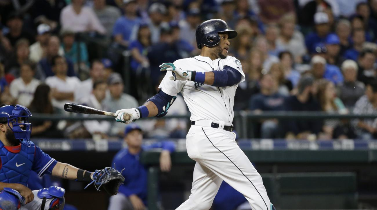 Seattle Mariners' Robinson Cano follows through on a two-run triple against the Toronto Blue Jays during the fifth inning of a baseball game Friday, July 24, 2015, in Seattle. (AP Photo/Elaine Thompson)