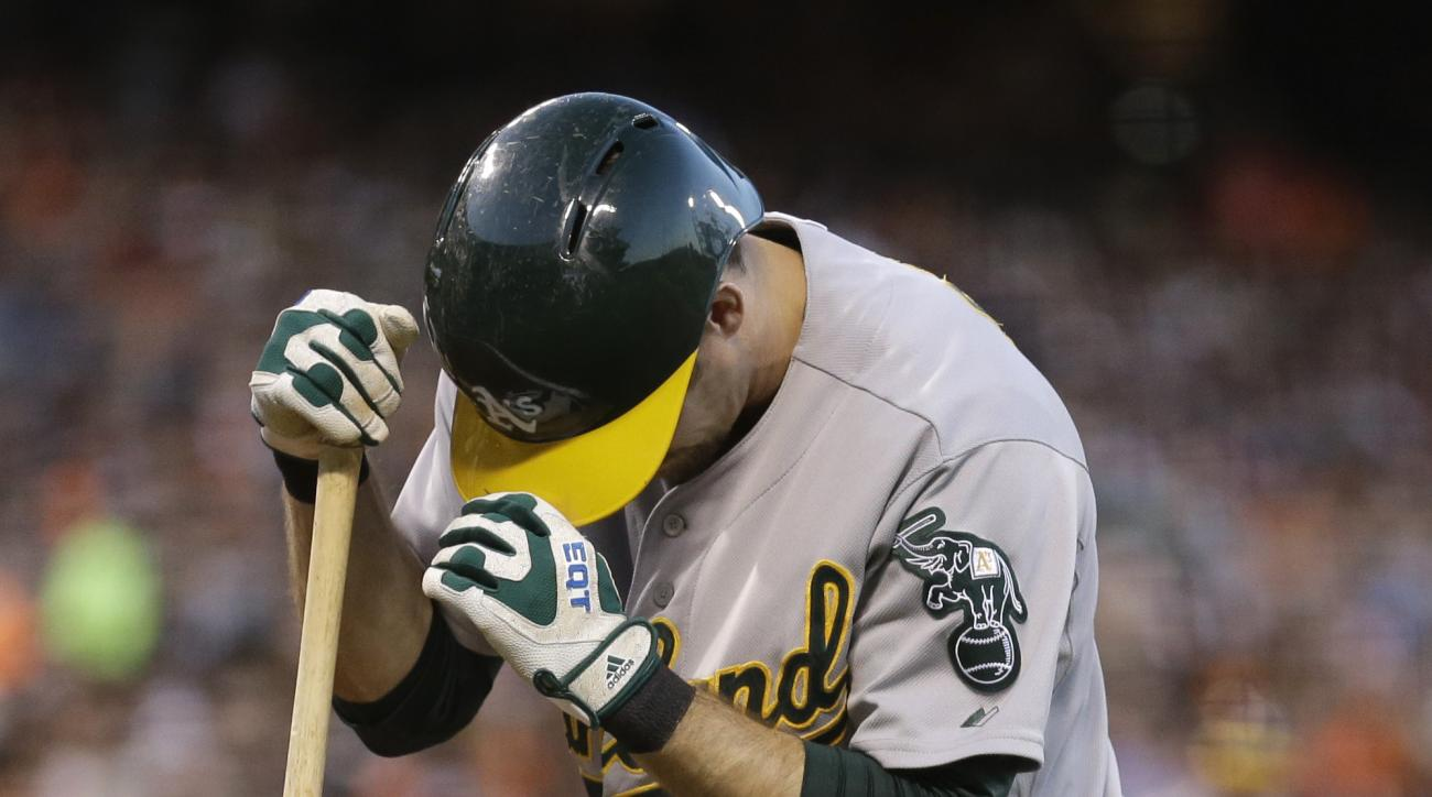 Oakland Athletics' Billy Burns kneels after being hit by a foul tip in the third inning of a baseball game against the San Francisco Giants Friday, July 24, 2015, in San Francisco. Burns left the game with a testicular contusion. (AP Photo/Ben Margot)