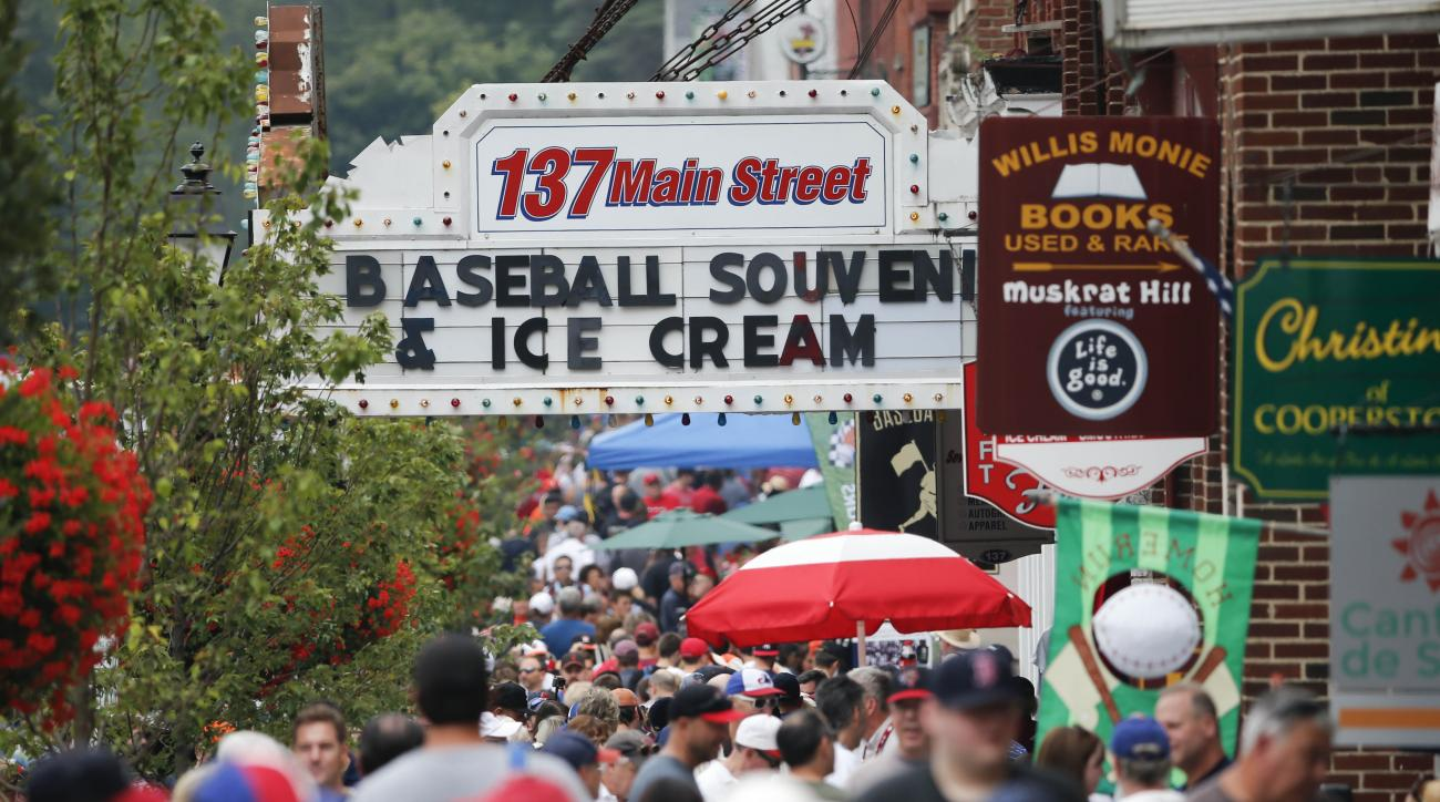 People walk along Main Street on Saturday, July 25, 2015, in Cooperstown, N.Y. The National Baseball Hall of Fame holds its induction ceremony on Sunday. (AP Photo/Mike Groll)