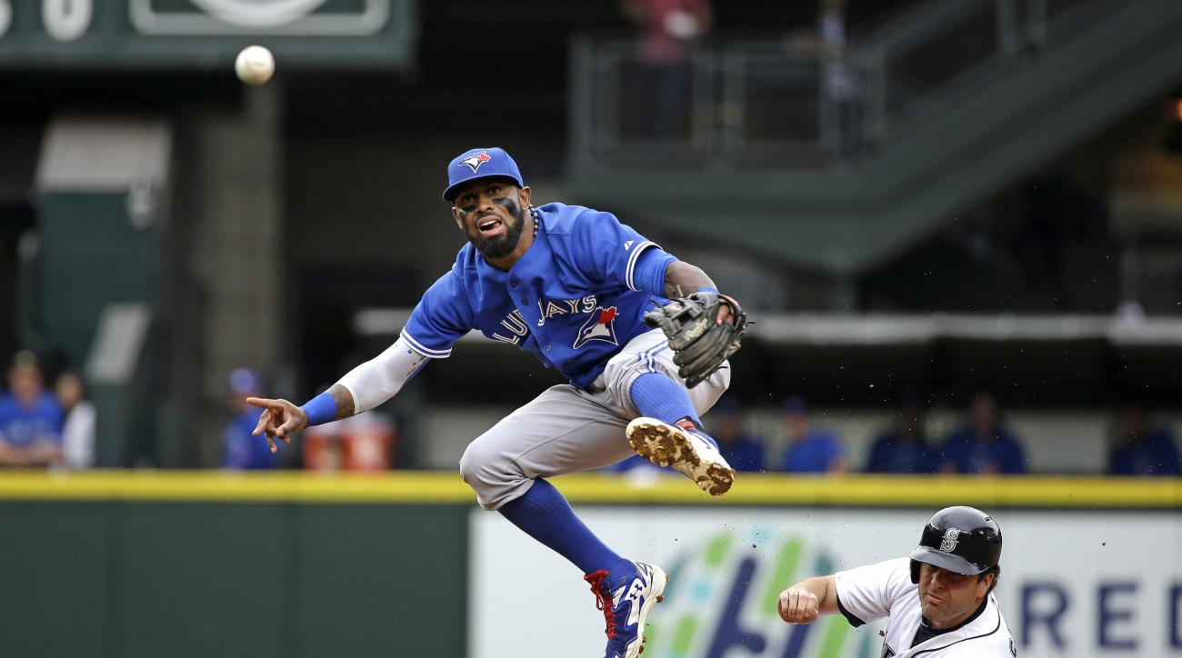 Toronto Blue Jays shortstop Jose Reyes, left, leaps out of the way after forcing out Seattle Mariners' Seth Smith at second base and throwing to first in the third inning of a baseball game Saturday, July 25, 2015, in Seattle. Logan Morrison was safe at f