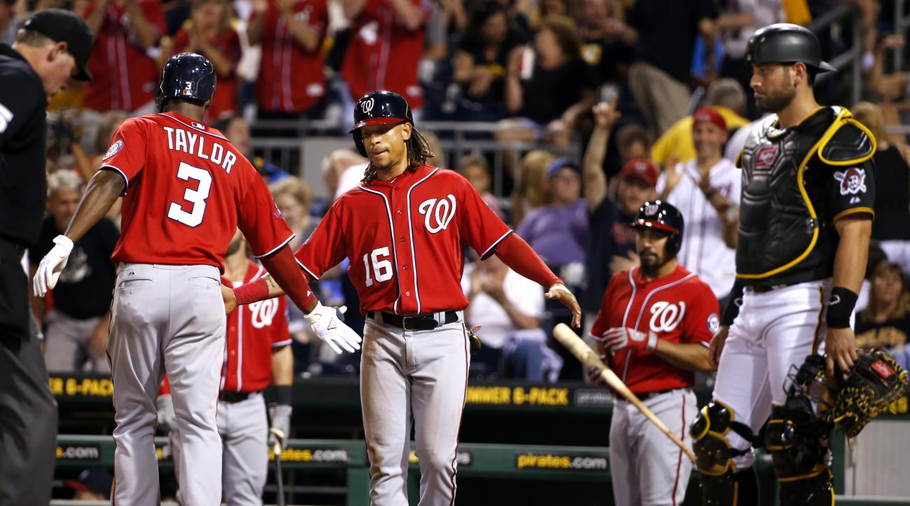 Washington Nationals' Michael Taylor (3) celebrates with teammate Emmanuel Burriss (16) after hitting a two-run home run off Pittsburgh Pirates relief pitcher Arquimedes Caminero in the eighth inning of a baseball game in Pittsburgh, Saturday, July 25, 20
