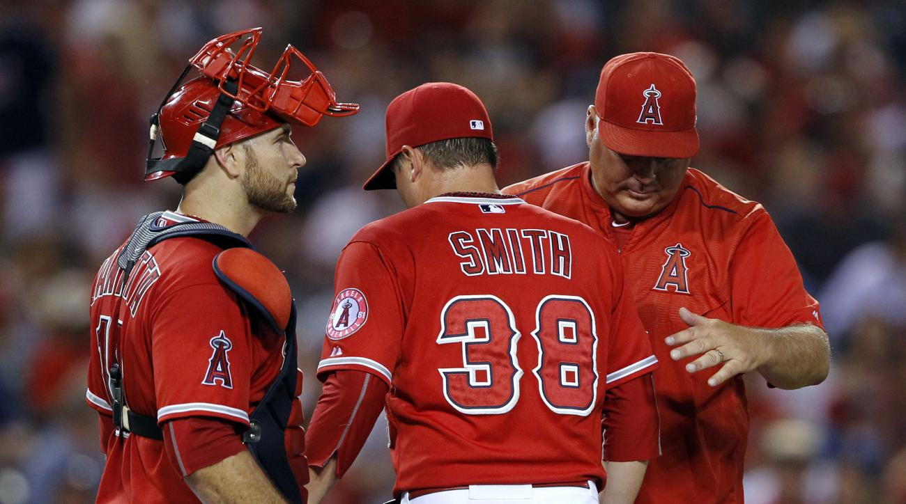 Los Angeles Angels manager Mike Scioscia, right, removes relief pitcher Joe Smith (38) with catcher Chris Iannetta also at the mound during the eighth inning of a baseball game against the Texas Rangers in Anaheim, Calif., Saturday, July 25, 2015. (AP Pho