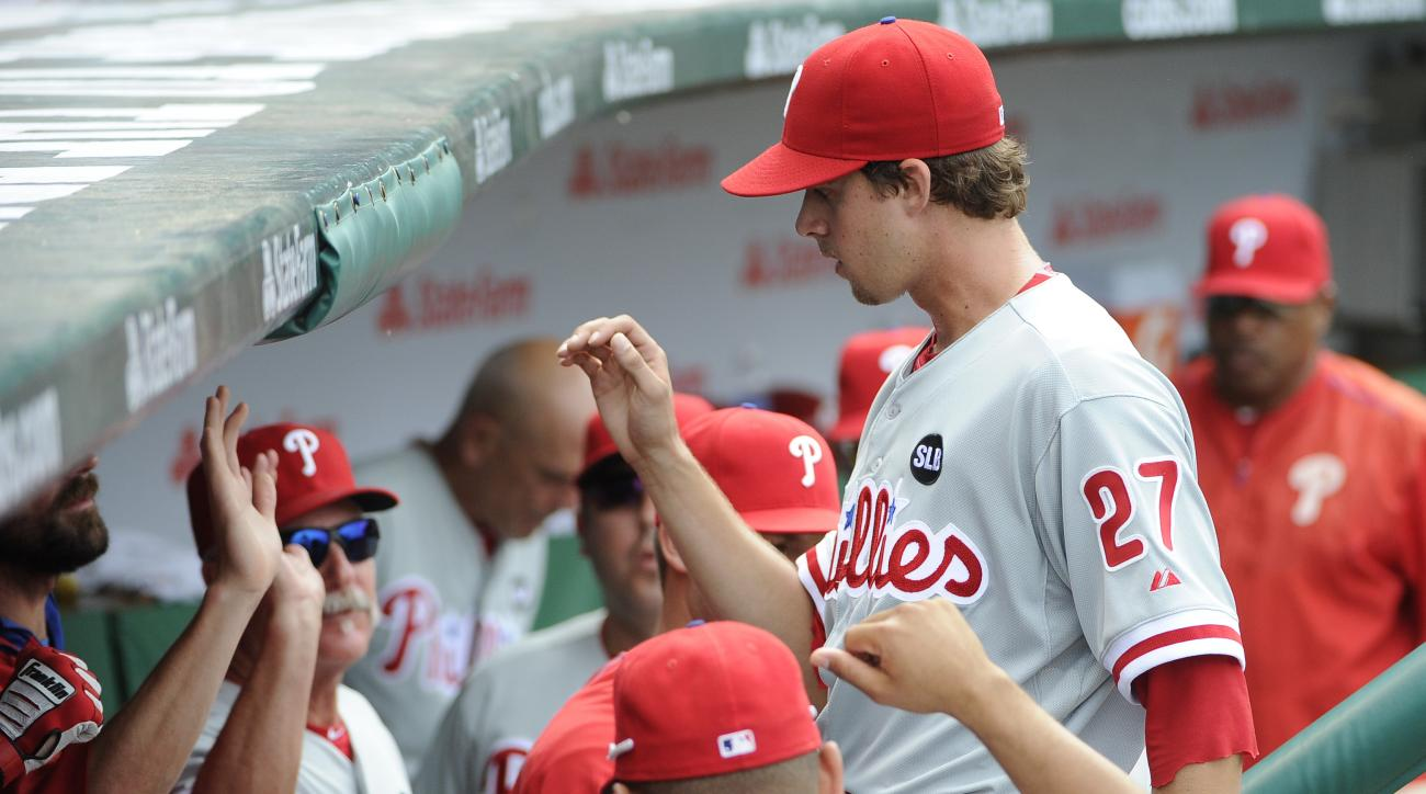 Philadelphia Phillies starting pitcher Aaron Nola (27) is greeted by coaches and teammates after leaving during the eighth inning of a baseball game against the Chicago Cubs, Sunday, July 26, 2015, in Chicago. (AP Photo/David Banks)