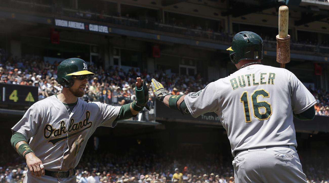 Oakland Athletics' Ben Zobrist, left, is congratulated by Billy Butler after scoring against the San Francisco Giants during the fourth inning of a baseball game in San Francisco, Sunday, July 26, 2015. (AP Photo/Jeff Chiu)