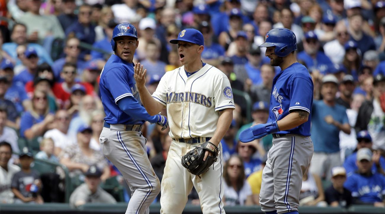 Seattle Mariners third baseman Kyle Seager, center, yells for the ball to come his way as both Toronto Blue Jays Ezequiel Carrera, left, and Kevin Pillar stand at third base in the fourth inning of a baseball game Sunday, July 26, 2015, in Seattle. Both p