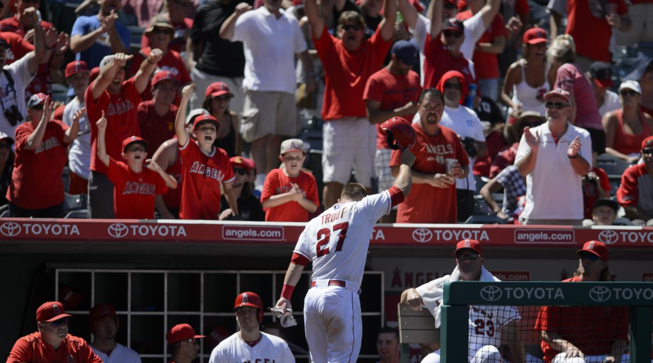 Los Angeles Angels' Mike Trout, center, acknowledges the fans after hitting a grand slam home run during the sixth inning of a baseball game against the Texas Rangers in Anaheim, Calif., Sunday, July 26, 2015. (AP Photo/Kelvin Kuo)
