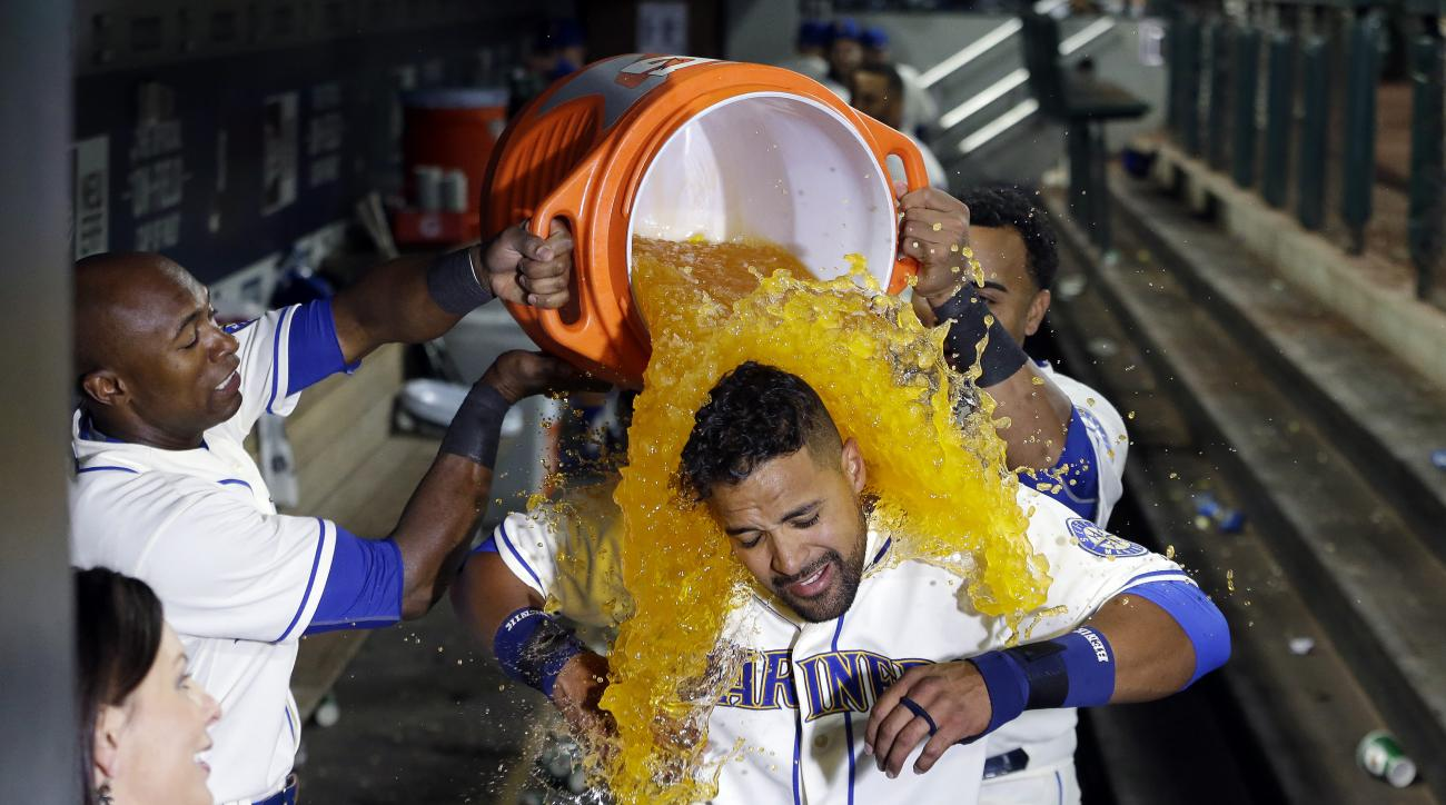 Seattle Mariners' Franklin Gutierrez, center, is doused with a bucket of a sports drink by teammates Austin Jackson, left, and Nelson Cruz after Gutierrez's home run that beat the Toronto Blue Jays in the 10th inning of a baseball game Sunday, July 26, 20