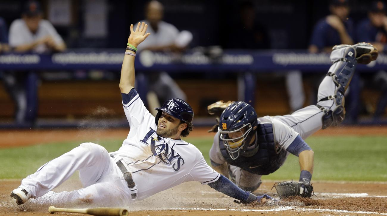 Tampa Bay Rays' David DeJesus, left, slides around the tag from Detroit Tigers catcher Alex Avila while scoring on an RBI single by Logan Forsythe during the fifth inning of a baseball game Monday, July 27, 2015, in St. Petersburg, Fla.  (AP Photo/Chris O