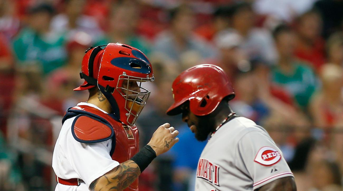 St. Louis Cardinals catcher Yadier Molina, left, looks on as Cincinnati Reds' Brandon Phillips scores on a sacrifice fly by Jay Bruce during the third inning of a baseball game against the St. Louis Cardinals, Monday, July 27, 2015, in St. Louis. (AP Phot