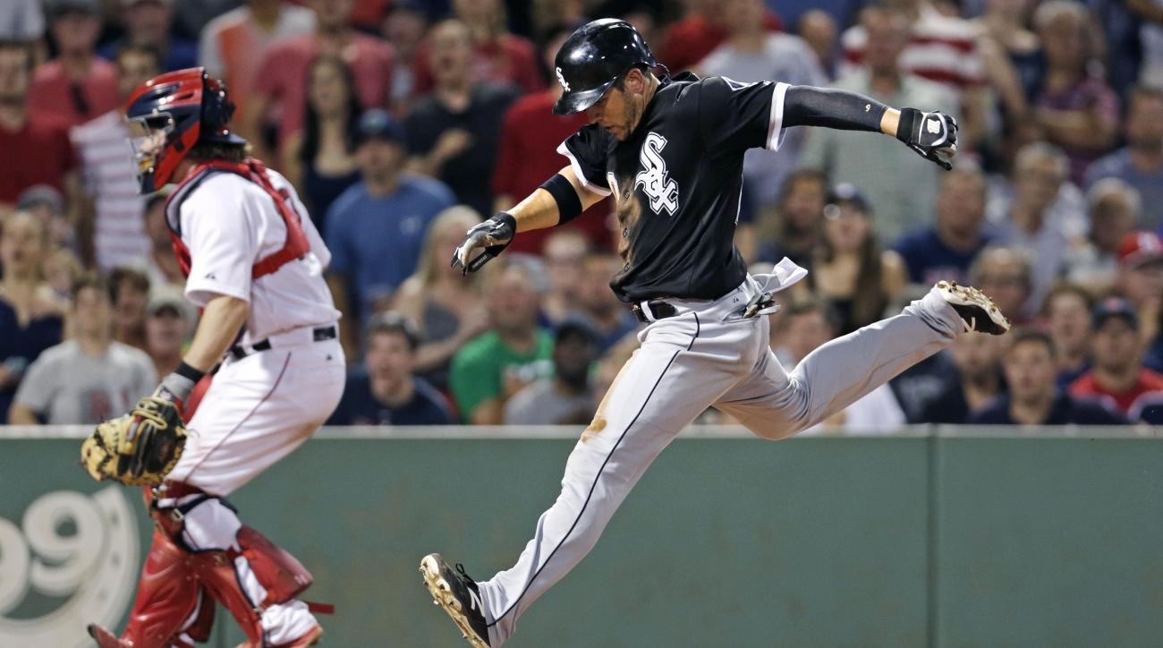 Chicago White Sox's J.B. Shuck scores on a single by teammate Tyler Flowers, as Boston Red Sox catcher Ryan Hanigan, left, looks for the ball during the seventh inning of a baseball game at Fenway Park in Boston, Monday, July 27, 2015. (AP Photo/Charles K