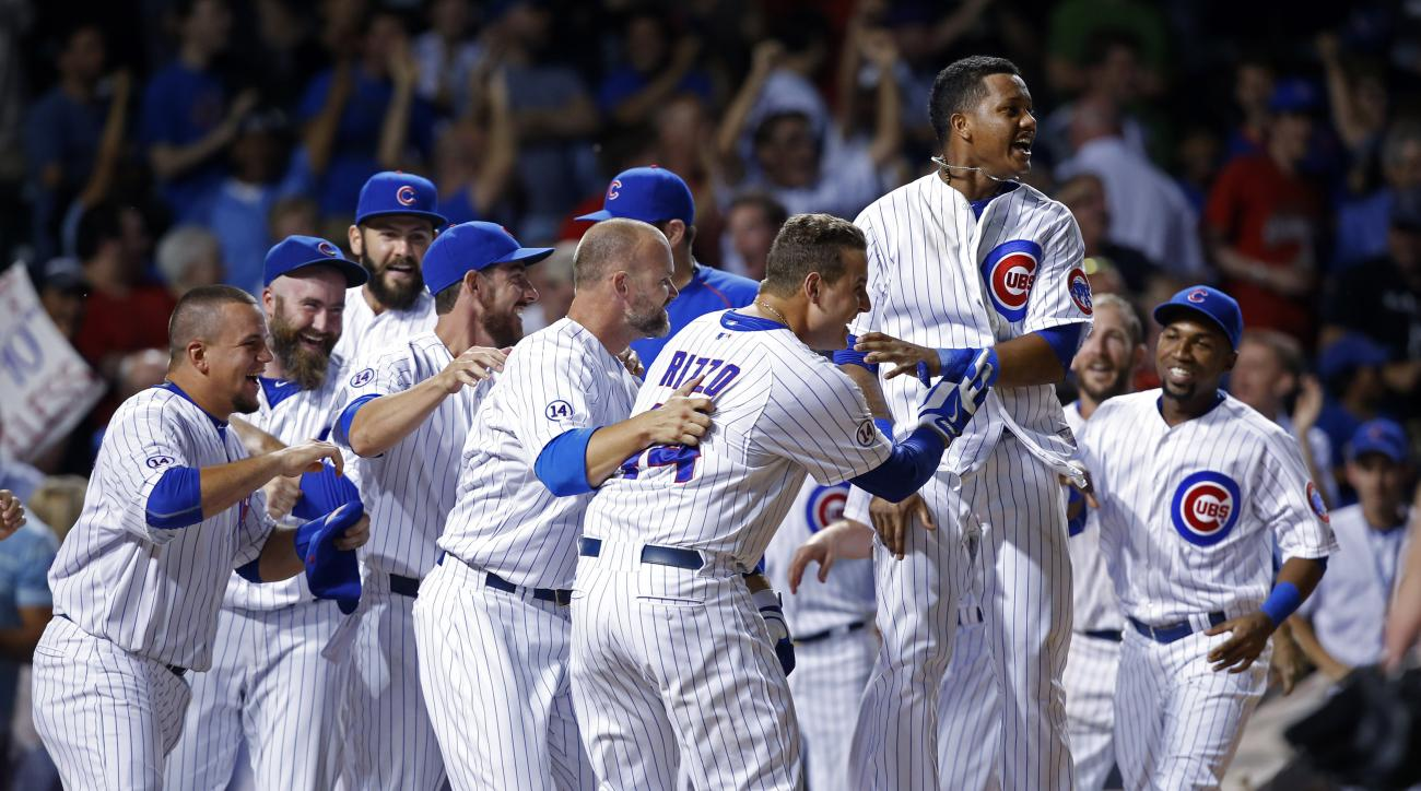 Chicago Cubs players including Anthony Rizzo, center, and Starlin Castro, right of center, celebrate after Kris Bryant hit a game winning two run home run against the Colorado Rockies during the ninth inning of a baseball game in Chicago, Monday, July 27,