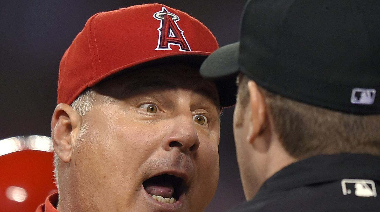 FILE - In this June 12, 2015, file photo, Los Angeles Angels manager Mike Scioscia, left, argues with an umpire during the sixth inning of a baseball game against the Oakland Athletics in Anaheim, Calif. On Tuesday, July 28, 2015, a computer will stand in
