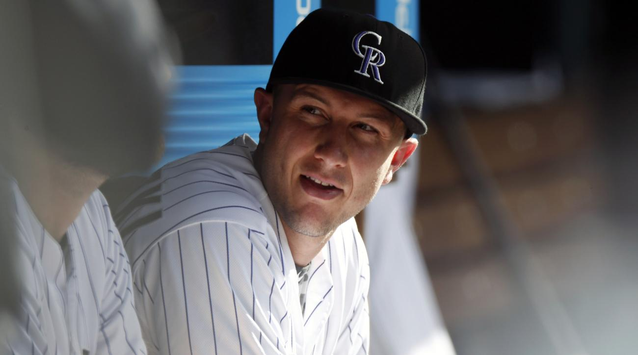 In this photograph taken Sunday, July 26, 2015, Colorado Rockies shortstop Troy Tulowitzki looks on against the Cincinnati Reds in the seventh inning of a baseball game in Denver. Tulowitzki was traded along with relief pitcher LaTroy Hawkins to the Toron