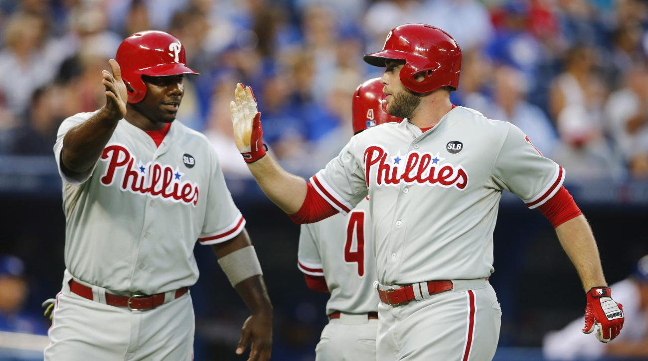 Philadelphia Phillies Ryan Howard, left, and Darin Ruf, celebrate scoring against the Toronto Blue Jays during the third inning of an interleague baseball game, Tuesday, July 28, 2015 in Toronto. (Mark Blinch/The Canadian Press via AP) MANDATORY CREDIT