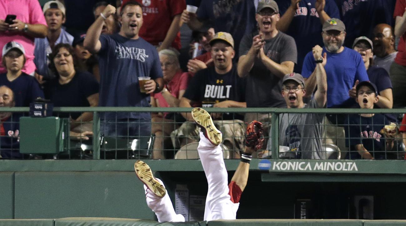 Boston Red Sox center fielder Mookie Betts flips over the bullpen wall while trying to field a drive by Chicago White Sox's Jose Abreu during the sixth inning of a baseball game at Fenway Park in Boston, Tuesday, July 28, 2015. Umpires ruled the play a ho