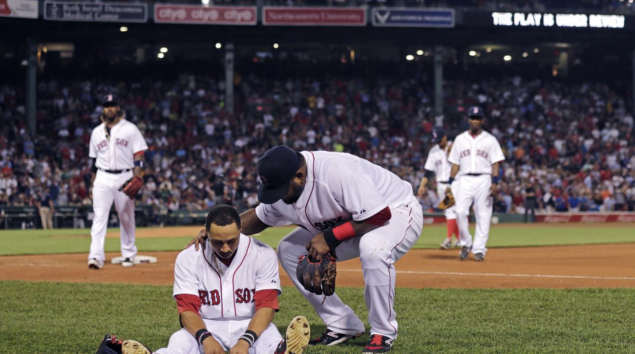 Boston Red Sox center fielder Mookie Betts sits on the infield as teammate Pablo Sandoval checks to see if he's injured following a play where Betts flipped over the bullpen wall while trying to catch a drive by Chicago White Sox's Jose Abreu during the s