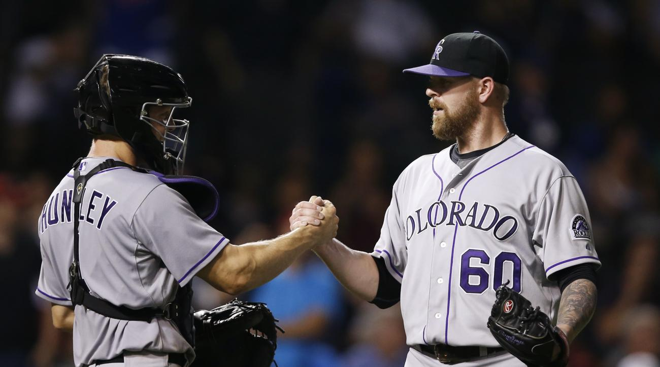 Colorado Rockies relief pitcher Justin Miller (60) and catcher Nick Hundley (4) celebrate after defeating the Chicago Cubs in a baseball game in Chicago, Tuesday, July 28, 2015. The Rockies won 7-2. (AP Photo/Andrew A. Nelles)
